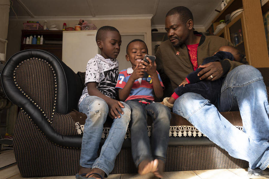 Dieu-Merci Matala, 44, holds his 7-month-old daughter, Grace, while her brothers David, 7 (far left), and Joshua, 4, play in the family's apartment in Maitland, Cape Town, South Africa in May 2019.