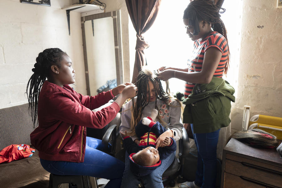 Fortune, left, and her mother, Bibiche, braid a client's hair at the family apartment in Cape Town, South Africa in May 2019.