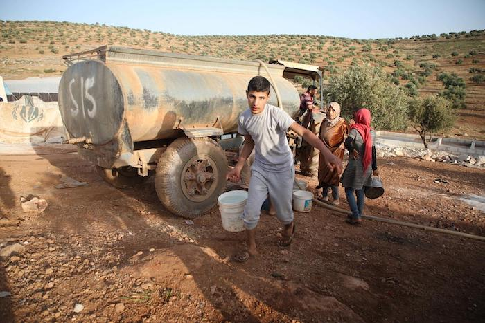 On 3 June 2019 in the Syrian Arab Republic, families fleeing hostilities in Idlib set-up a makeshift camp in Aqrabat village, 45km north of Idlib City, near the Turkish border. A water tanker provides clean water to displaced persons.