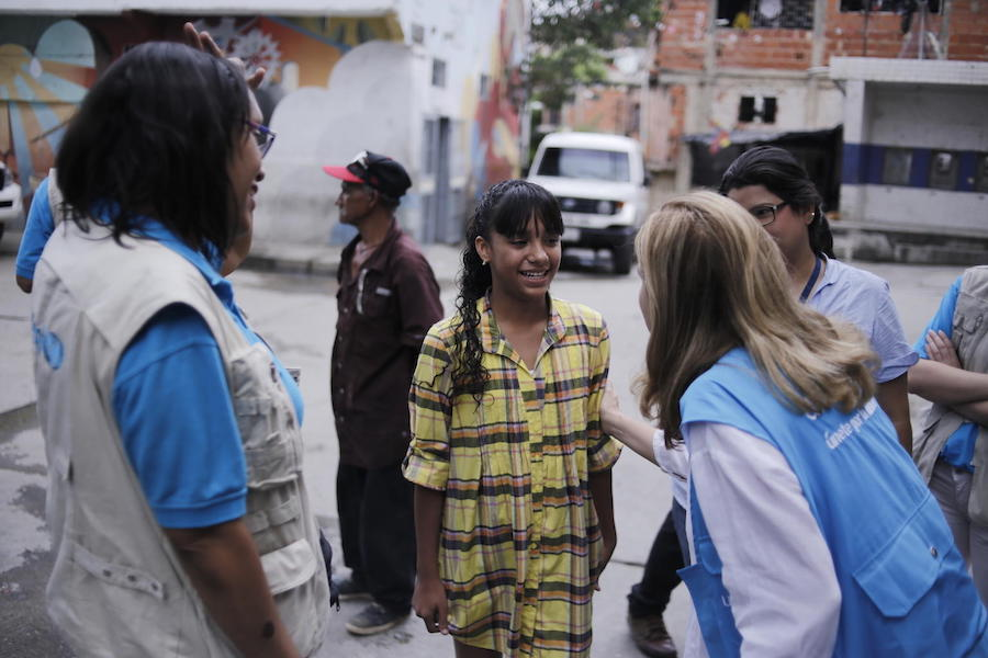 On June 4, 2019, Naibeth, 13 (center) meets with UNICEF staff near one of UNICEF's child protection centers in Caracas, Venezuela.