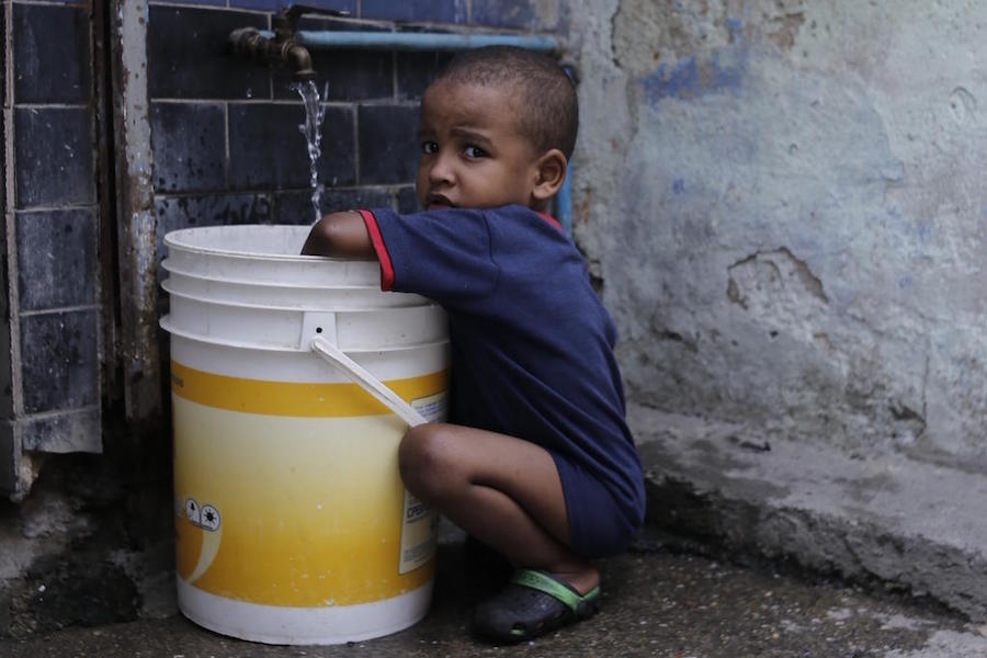 In June 2019, a child collects water in Petare, one of the most vulnerable neighborhoods in Caracas, Venezuela. UNICEF provided safe drinking water to 400,000 people in Venezuela in the first half of 2019.