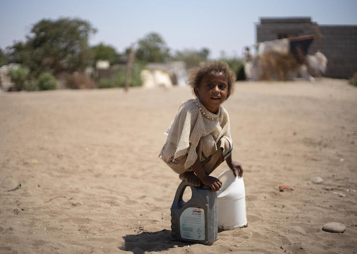 A child from Yemen's Al-Meshqafah camp plays while carrying water home from UNICEF-supported tanks in 2019.