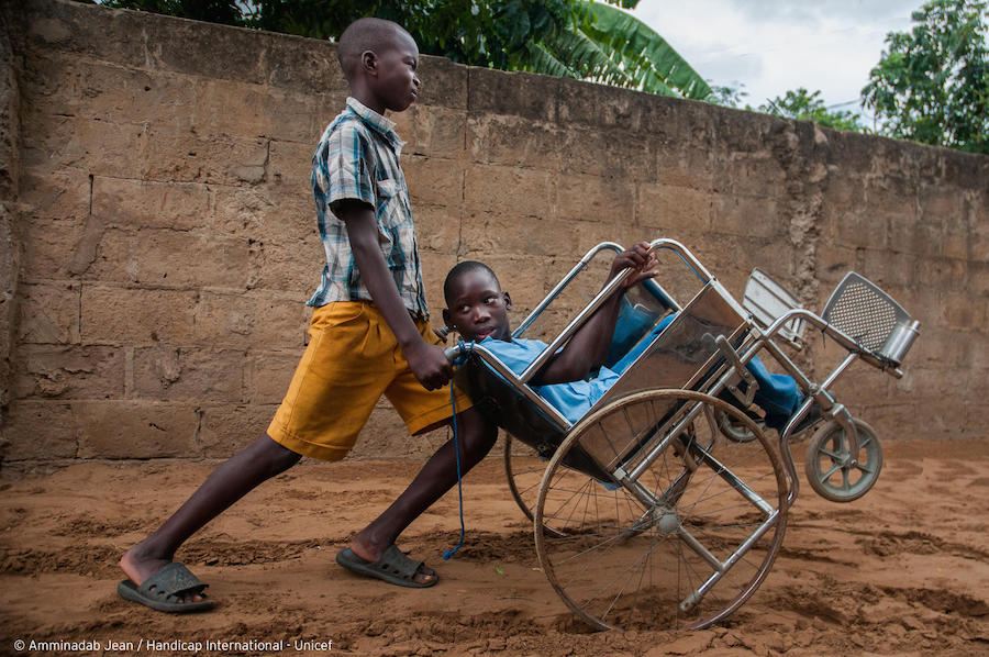 A friend pushes Ilídio, 11, in his wheelchair so he doesn't have to stay home in Mozambique in July, 2019.