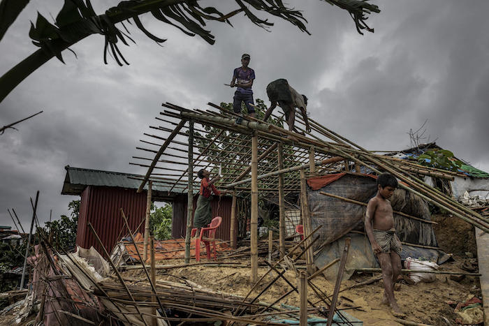 On July 7, 2019 in Bangladesh, men rebuild a house that was destroyed the night before by strong winds in Camp 18, part of the Kutapalong refugee camp in Cox's Bazar.