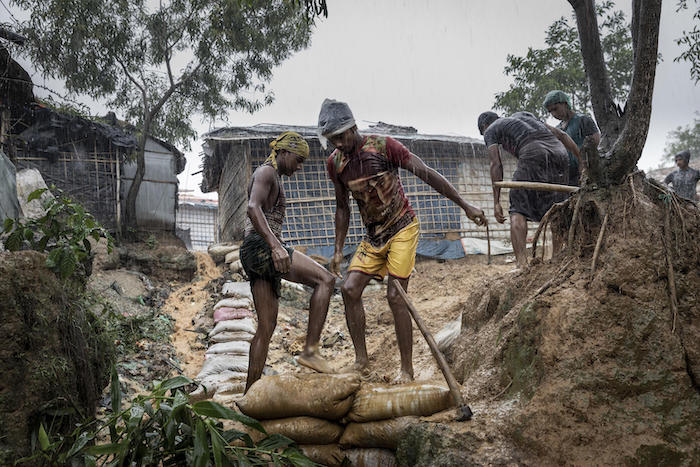 On 6 July 2019 in Bangladesh, two men reinforce a mountainside path in a flooded Rohingya camp in Cox's Bazar.