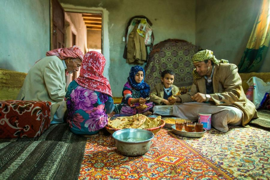 A family from Amran Governate in Yemen shares lunch on July 12, 2019. The family used money received through the Emergency Cash Transfer project to purchase food.