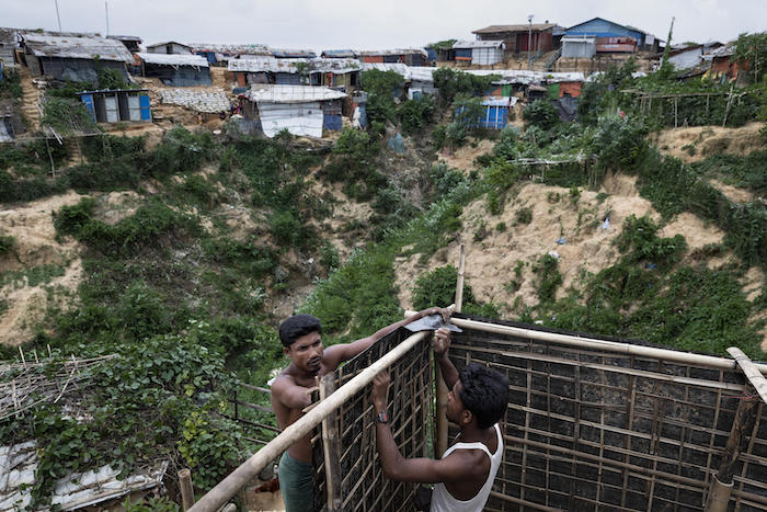 Imam Hosain (left), 27, and his brother Jahiruddin, 21, are building a family bathing room for both the females and males in their family in the hilly Hakimpara Rohingya refugee camp, Cox's Bazar, Bangladesh, June 2019.