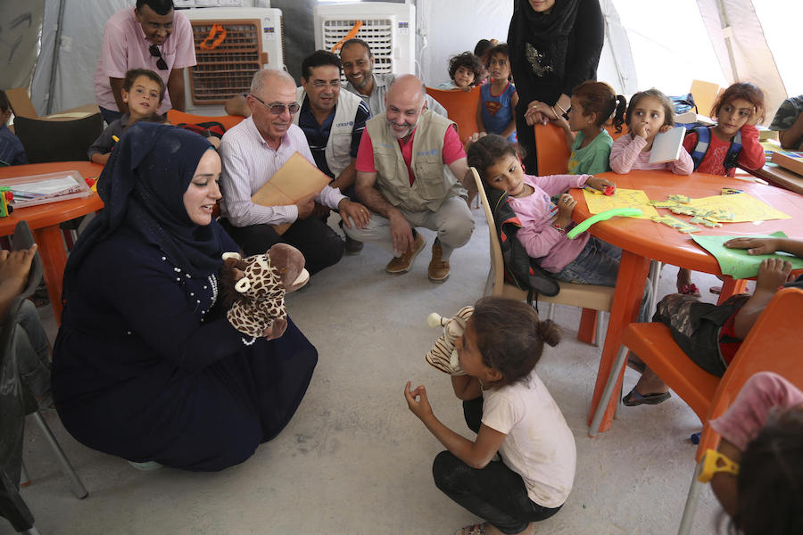 In July 2019, UNICEF Syria Representative Fran Esquiza (in red shirt) and colleagues watches as a UNICEF-supported social worker and a child perform a puppet show in Al-Hol camp in northeastern Syria.
