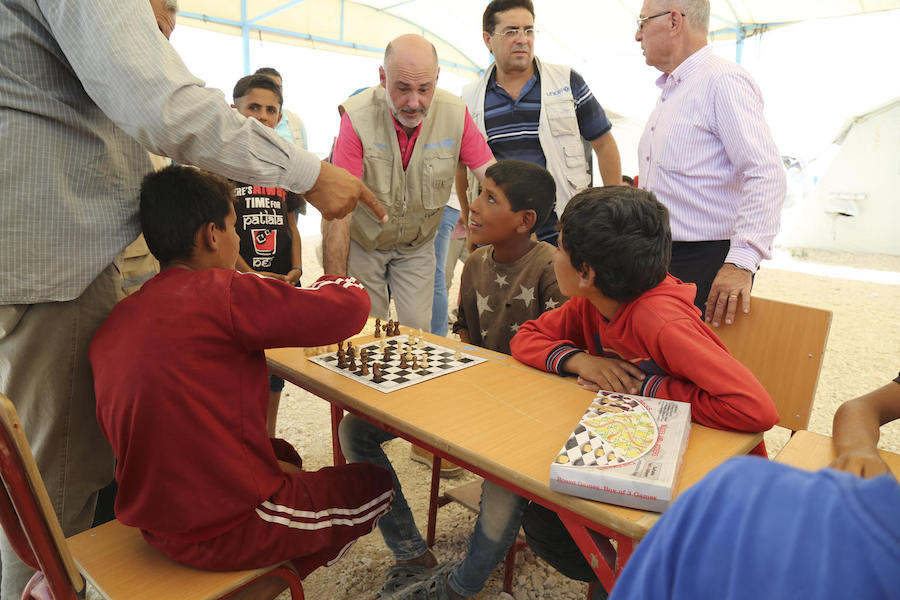 UNICEF Syria Representative Fran Aquiza (center) chats with children playing chess at a UNICEF-supported psychosocial support center in Al-Hol camp, northeastern Syria, in July 2019.