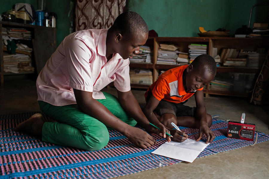 "Abdoulaye, 23, a radio school facilitator, guides Hussaini, 14, through lessons broadcast by a UNICEF-supported ""radio school"" in Dori, Burkina Faso."