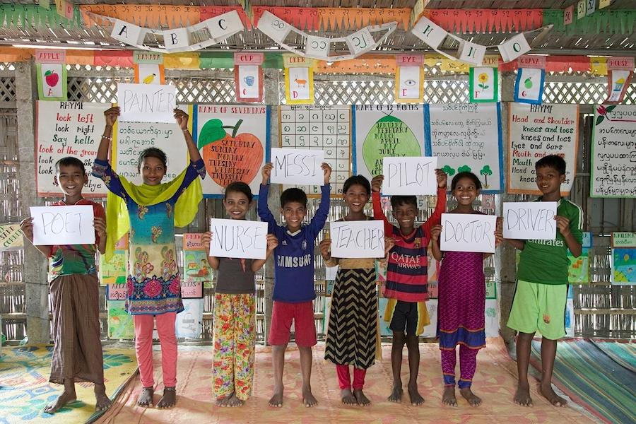 Rohingya refugee children attending UNICEF-supported learning centers in Cox's Bazar, Bangladesh hold signs sharing their hopes for the future.