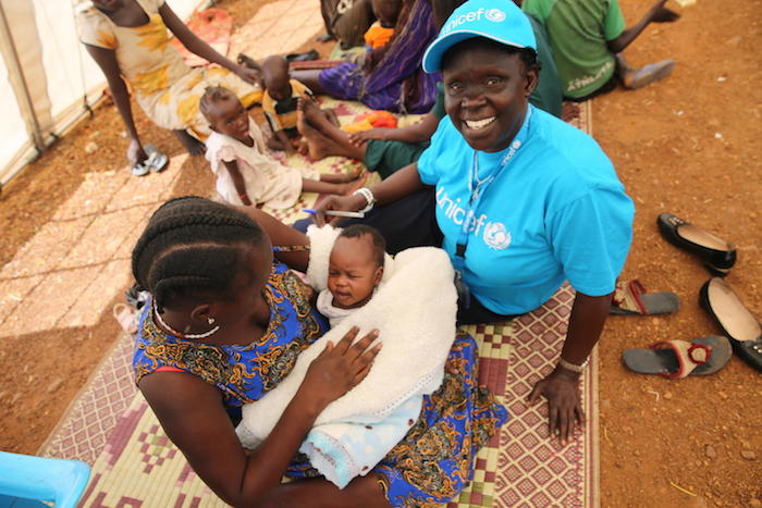 UNICEF staffer Cecilia Aldo visits with Anna Nyagma during a mother-to-mother community support group in South Sudan. Anna helps mobilize other mothers to join the meeting and practice exclusive breastfeeding.