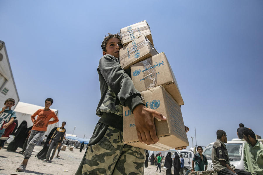 On July 22, 2019 in the Syrian Arab Repubic, a young boy collects a UNICEF-supported summer clothing kit at a refugee camp in Al, south of Hassakeh City.
