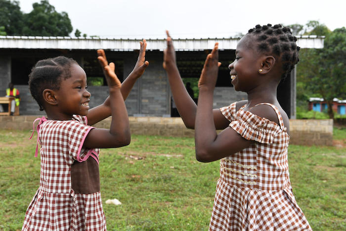 In Sangouine, Côte d'Ivoire, students play happily outside their new classrooms made of recycled plastic bricks through a UNICEF partnership with Conceptos Plasticos, a Columbian company.