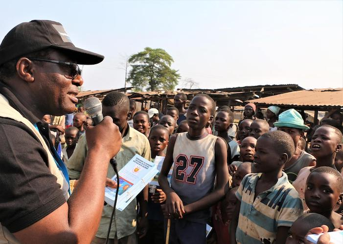 On August 7, 2019, Jean Louison Miango Makunda, UNICEF Burundi's Communication for Development (C4D) consultant on Ebola preparedness, speaks with children and distributes brochures in Gatumba, Burundi.