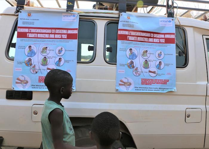 In Gatumba, Burundi, a boy examines posters as part of an Ebola awareness campaign organized by UNICEF Burundi's Communication for Development (C4D) team.