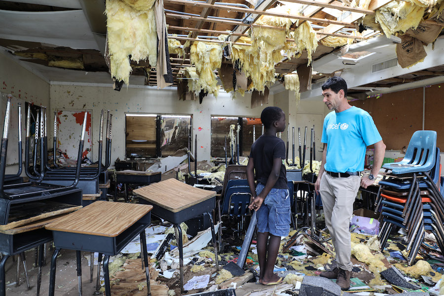 In the aftermath of Hurricane Dorian, Torres Sanvilla, 10, talks to UNICEF's Regional Emergency Specialist Hanoch Barlevi as they survey the damage to the classrooms of Central Abaco public school.