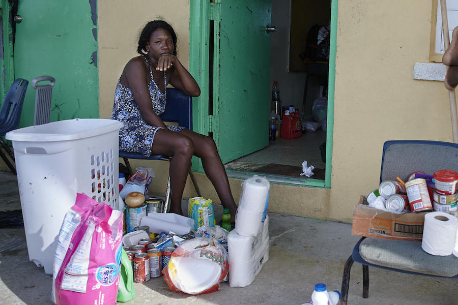 On September 8, 2019, Marie Evelyn, 46, sits outside a classroom at the Central Abaco Primary School, a temporary shelter in Marsh Harbour, Abaco Island, the Bahamas, after Hurricane Dorian her family's home.