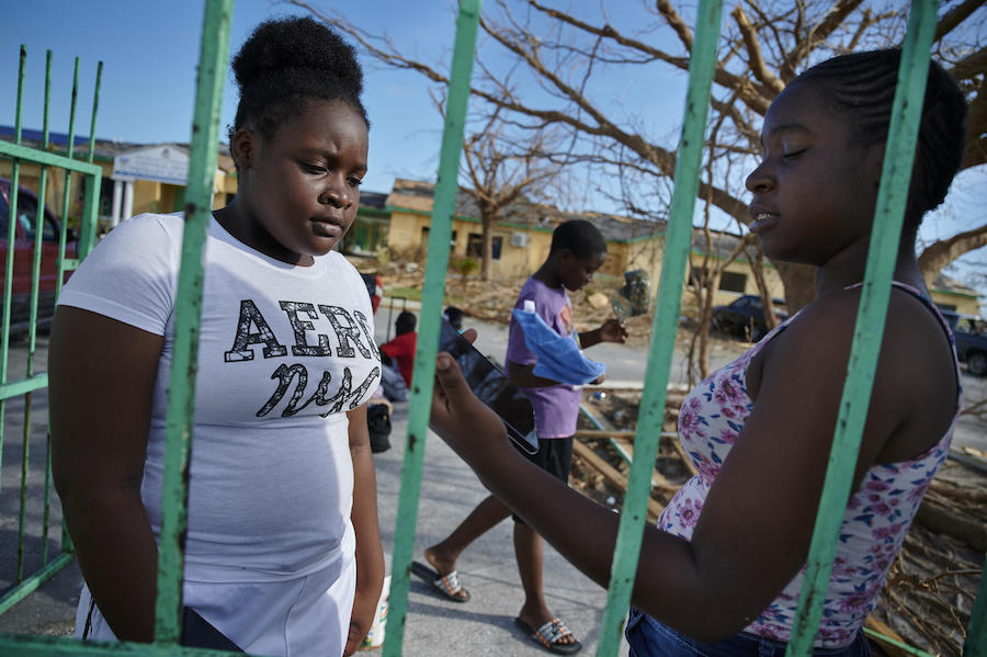 On September 8, 2019 in the Bahamas, Metory, 16, (right) speaks to her younger sister, Brianna, 14, outside the Central Abaco Primary School, a temporary shelter in Marsh Harbour.