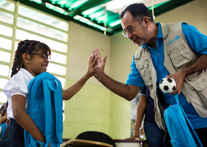 UNICEF Education Officer Dario Moreno high-fives Yeiberling, 9, after giving her a Back-to-School kit in Baruta, Venezuela in September 2019.
