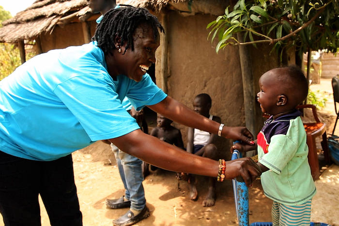 Ten-month-old Akot plays with UNICEF nutritionist Jesca Wude Murye outside Akot's home in Aweil, South Sudan in September 2019.