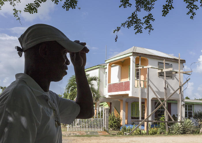 On November 7, 2019, James Gerald, Sr. stands in front of his family's home on the island of Barbuda. Since being evacuated following Hurricane Irma in September 2017, Gerald's wife and children have been living in Antigua.