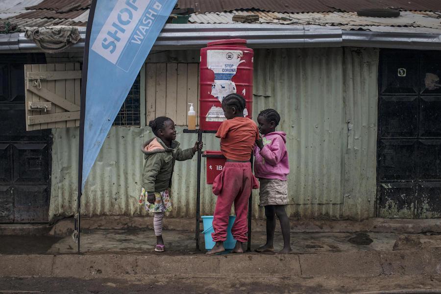 On 28 September 2020, children use a tank-based handwashing station in Kibera, the biggest informal settlement in Nairobi, Kenya.
