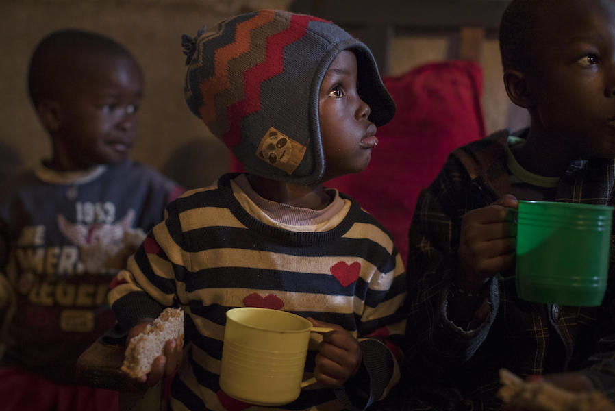 On 28 September 2020 in Kenya, Chris Omondi (center), 7, drinks water while having breakfast with his siblings in their home in Kibera, the largest informal settlement in Nairobi.