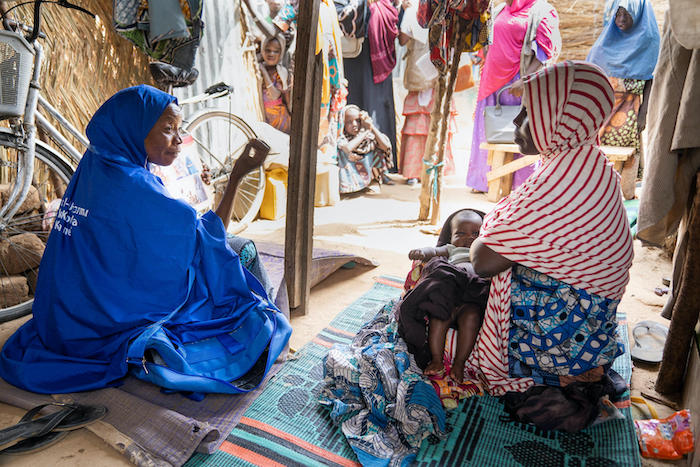 At the Gubio displacement camp in Borno State, Nigeria, a Volunteer Community Mobilizer speaks to a mother about the importance of immunizing her infant son against polio.