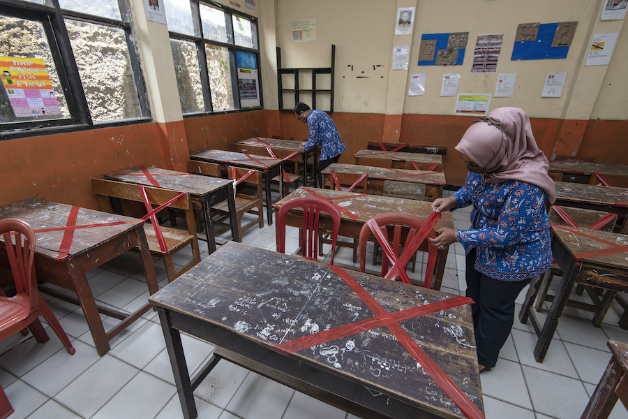 Teachers at SDN Sukamaju primary school in  Bandung, West Java province, Indonesia, mark classroom desks and chairs to ensure that students keep 6 ft. apart from each other to prevent the spread of coronavirus.