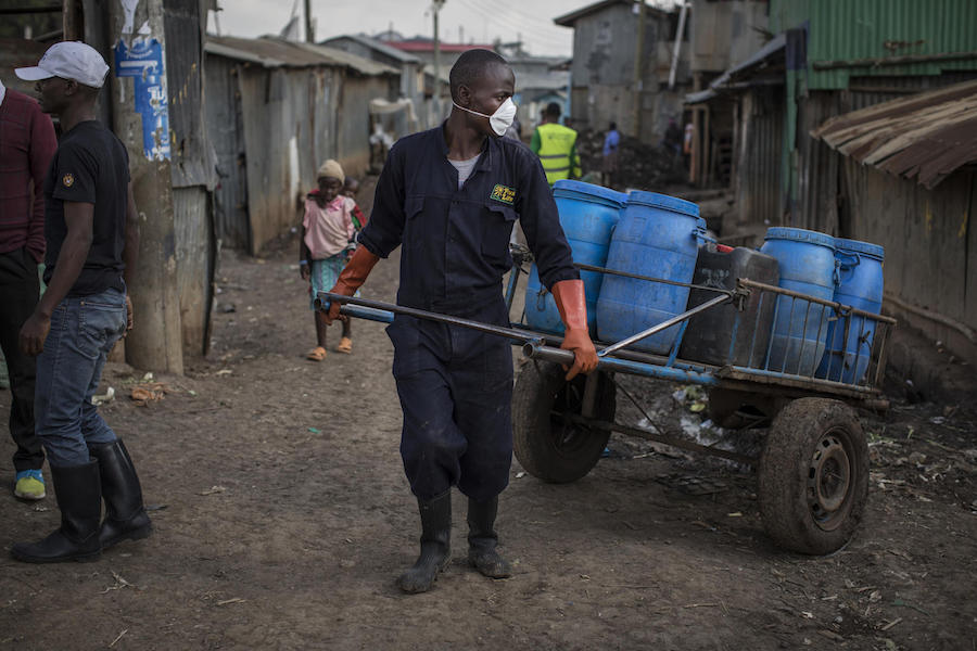 On 1 October 2020 in Kenya, Wiseman Jirungu (center), 26, a Sanergy sanitation employee, collects waste from, and cleans, Fresh Life toilets in Mukuru kwa Ruben, an informal settlement on the outskirts of Nairobi.