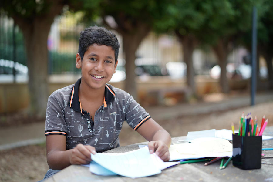 Hussein, 12, proudly shows his drawings at the UNICEF Child-Friendly Space in Beirut's Karantina Municipal Park on October 28, 2020.