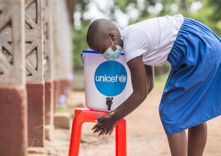 On November 10, 2020, a student washes her hands at a UNICEF-supplied hygiene station outside Elikya I Primary School in Mbandaka, Democratic Republic of Congo.