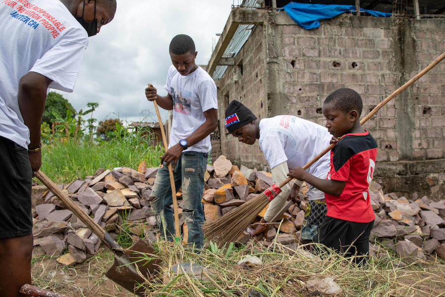 A group of young children from Kinshasa, Democratic Republic of the Congo, pause their clean-up activities to take a photo. The group, who range in age from 4 to 18, meet every Saturday morning to remove waste and discarded debris from their neighborhoods