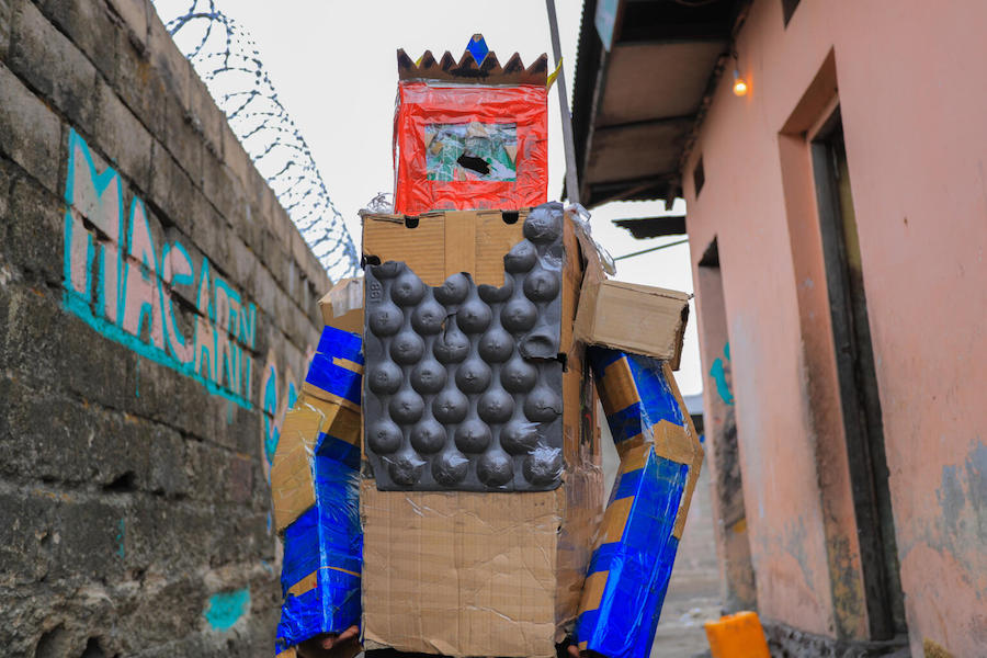 In DRC's capital city of Kinshasa, Peggy, 16, collects cardboard boxes littered throughout her neighborhood to create wearable art that sends a powerful message to her community.