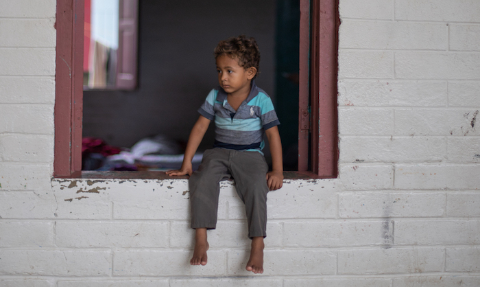 A boy whose family lost everything when Hurricans Eta and Iota swept through Honduras sits in the window of a school now serving as a shelter for affected families.