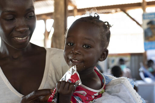 Jenty, 11 months old, eats Ready to Use Therapeutic Food in her mom's arms at a UNICEF nutrition center in Yambio, South Sudan. When her mother brought her to the center, she was diagnosed with acute malnutrition. But after a several-week course of therap
