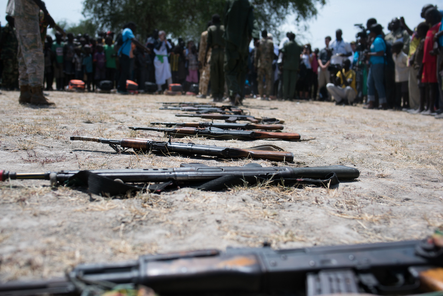 Children associated with the Cobra faction wait to be demobilized in Pibor, their weapons are seen on the ground. A total of 145 children from the Cobra Faction and SPLA-IO were disarmed and released by the two armed groups.
