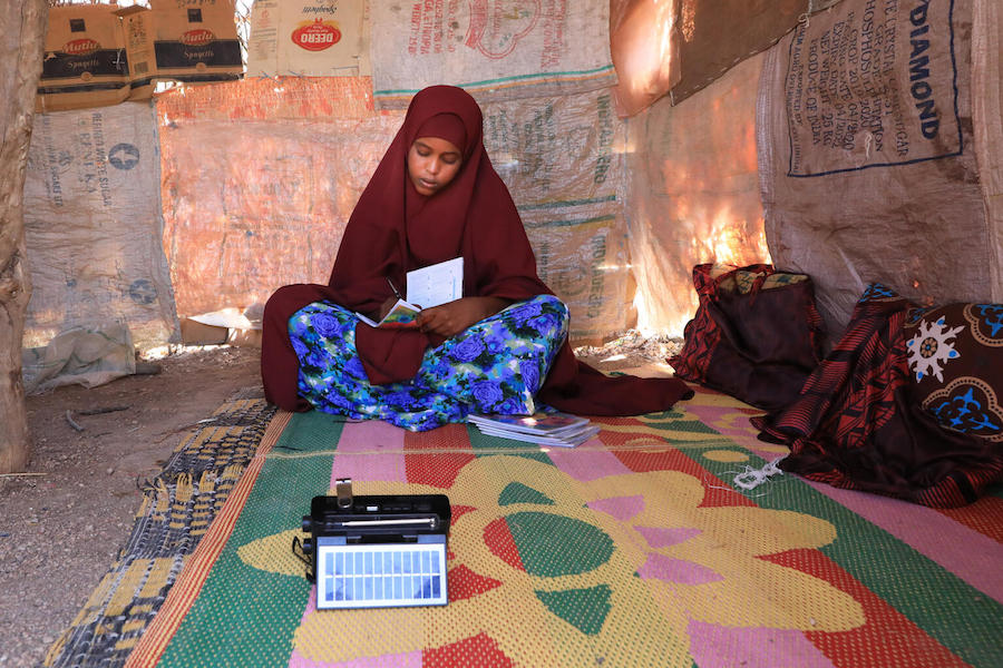 In Somalia, 14-year-old Farhia uses a small solar-powered radio provided by UNICEF and partners to listen to recorded lessons.