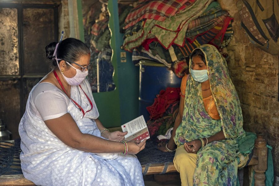 Heena Joshi 48 – year – old UNICEF health worker (Left) on routine home visits to check on Aruna Dodiyar 25 – year – old (Right) with her 2nd pregnancy to check the hemoglobin.