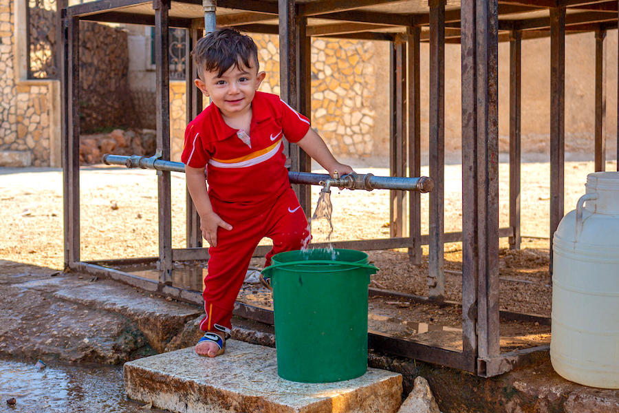 Five-year-old Hasan likes to help out by filling his family's water bucket from the tanks installed by UNICEF near his home in Fafin village, northern rural Aleppo.