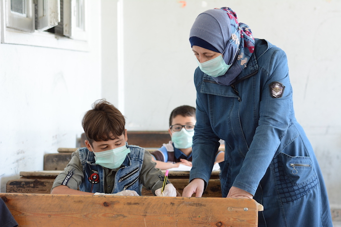 Najwa Almasri, principal of Adnan Almalki school in Hama city, helps a student during a UNICEF-supported 'Curriculum B' class, part of an accelerated learning program to help out-of-school kids catch up to peers..