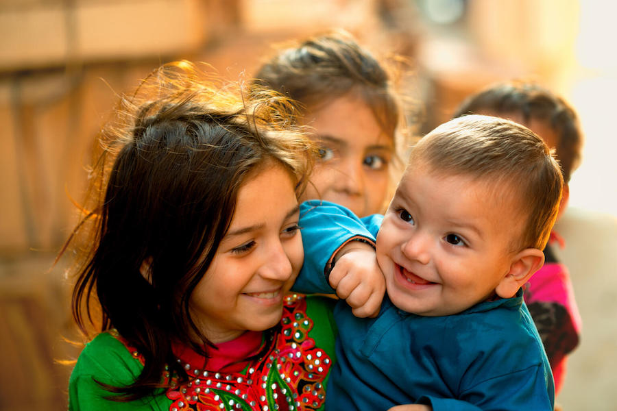 In Lahore, Pakistan in January 2021, a 1-year-old boy and his big sister share a laugh with a UNICEF-supported polio vaccinator.