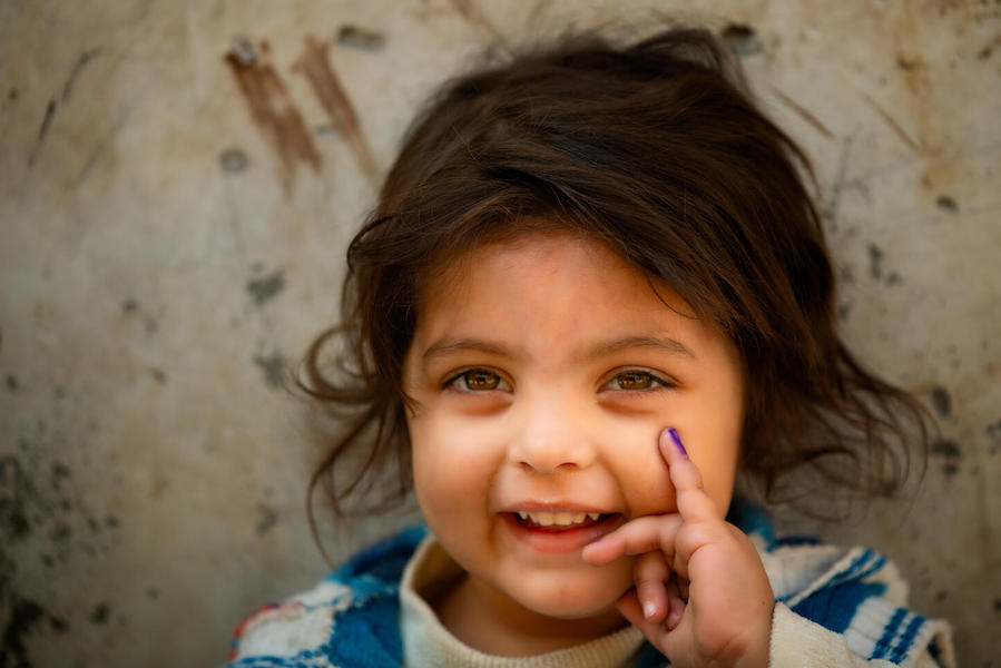In Lahore, Pakistan in January 2021, a 3-year-old girl shows her finger, marked in purple to indicate she has been vaccinated against polio.