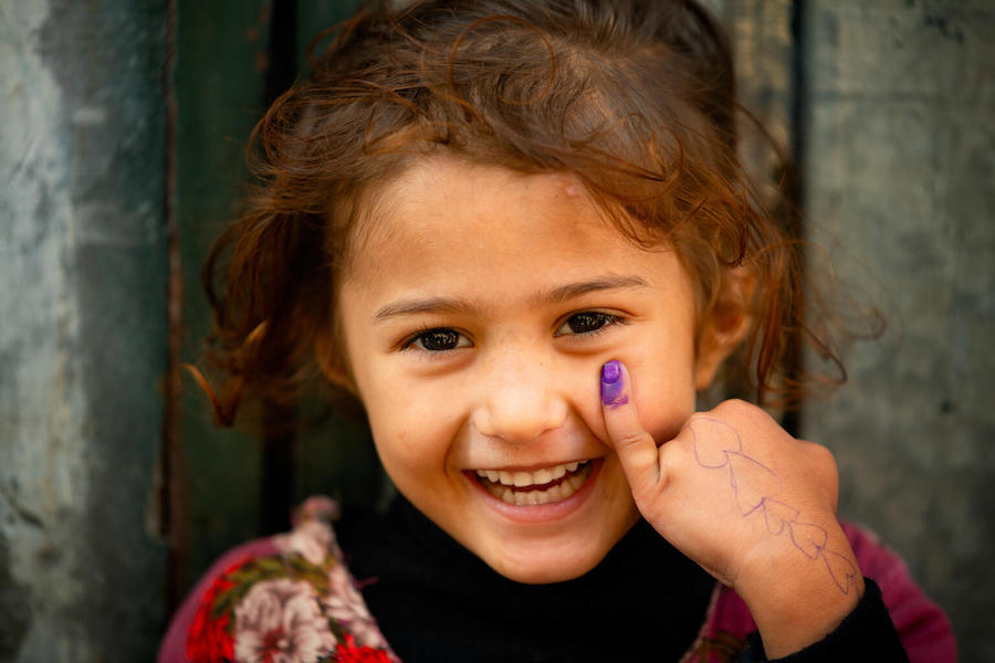 In Lahore, Pakistan, a 4-year old-girl smiles for the UNICEF camera showing her marked finger after receiving the polio vaccine.