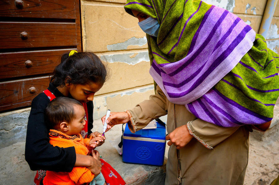 A UNICEF-trained vaccinator in Pakistan inks a child's finger to show he is now safe from polio.