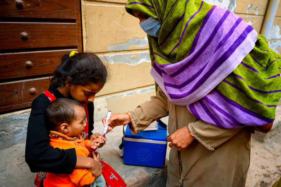 In January 2021, Shumaila, a polio vaccinator in Lahore, Pakistan, marks the finger of an 18-month old boy with the help of his sister, to show that he has received his vaccination.