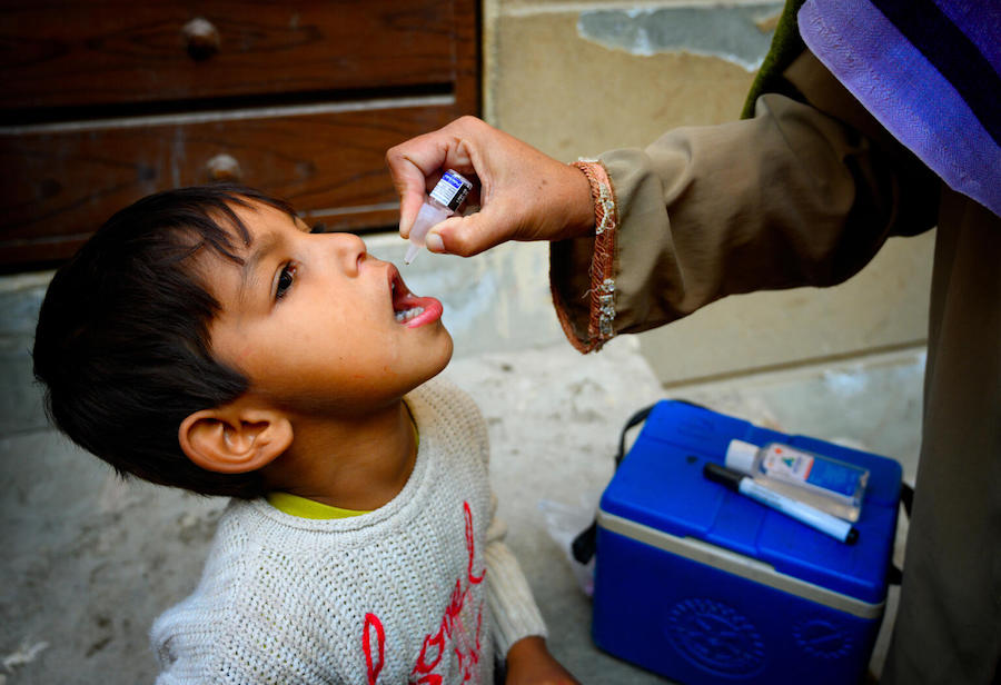 A 5-year-old boy receives the polio vaccine from Shumaila, a UNICEF-supported polio vaccinator in Lahore, Pakistan on January 11, 2021.