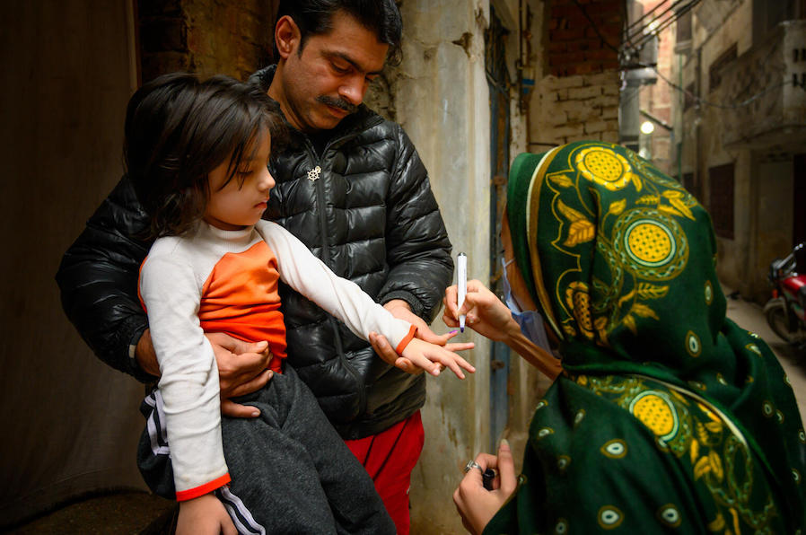 In January 2021, Sumaira, a polio vaccinator in Lahore, Pakistan, marks the finger of a 4-year-old with the help of the girl's father after vaccinating her with polio and giving her Vitamin A supplementation.