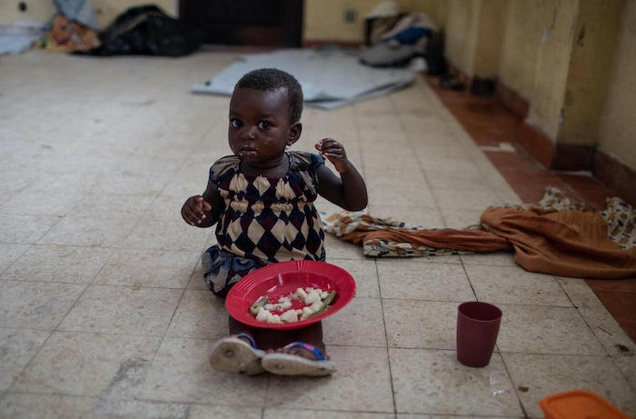 A girl sheltering in a school in Beira, Mozambique, during Cyclone Eloise receives food from emergency responders.
